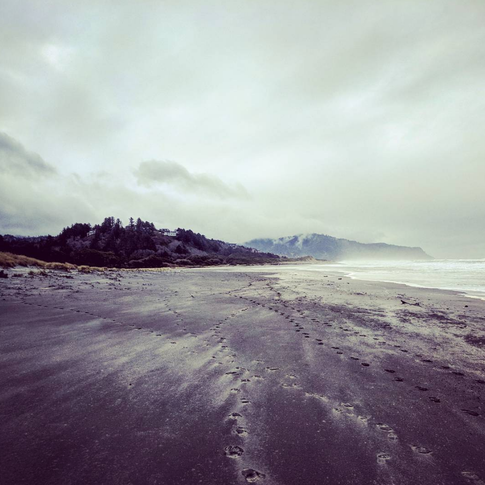 Windswept Oregon beach with footprints and wind patterns.