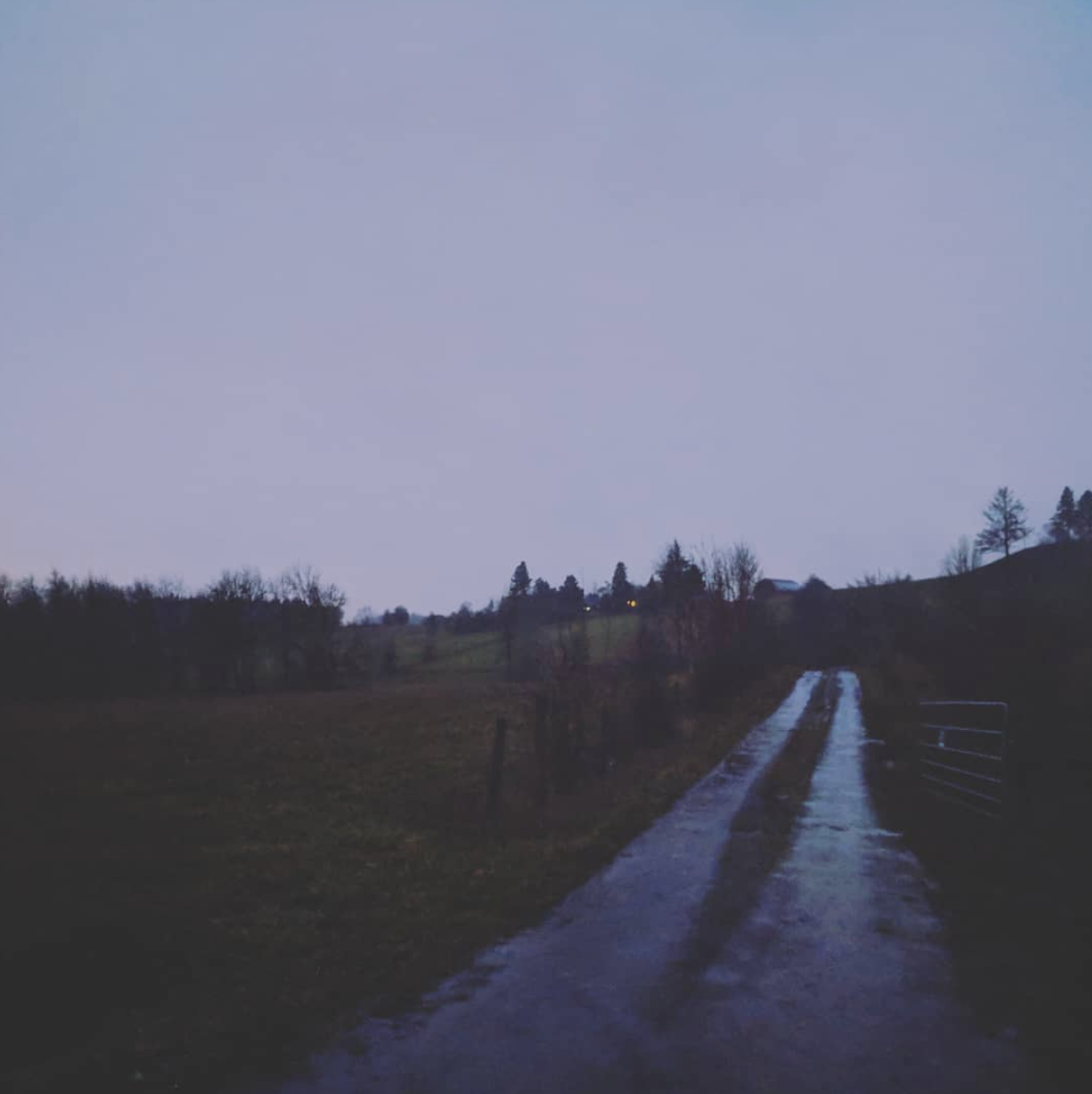 Rain-soaked gravel drive with purple sky and sodden fields all around.