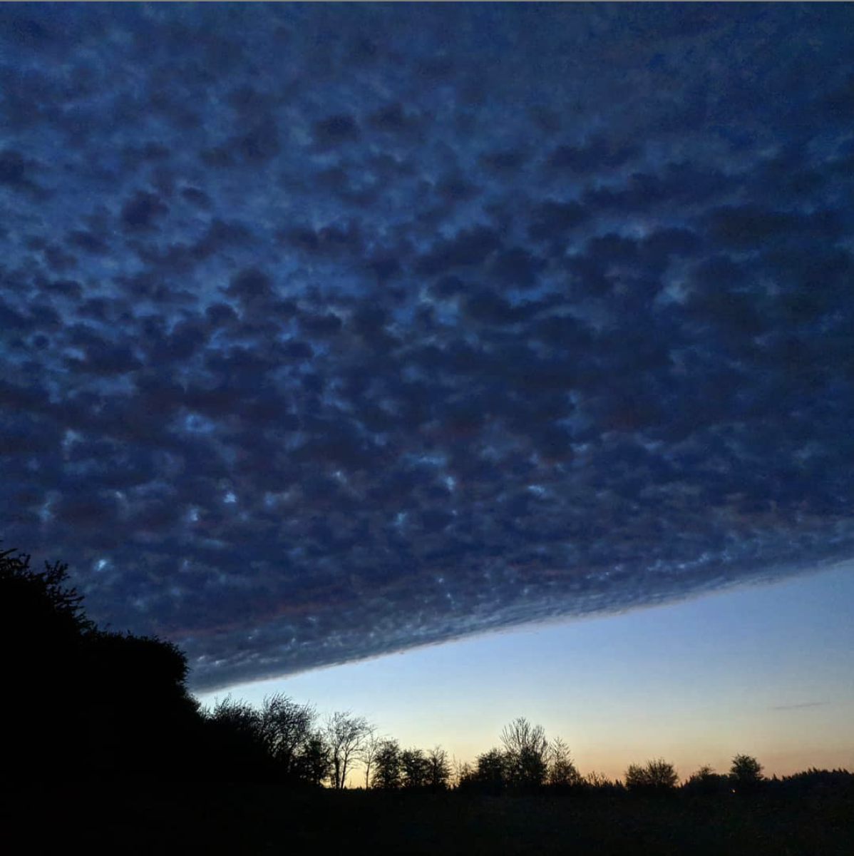 A diagonal veil of altocumulus divides day from night on a mid-April morning, just before sunrise. Photo copyright Tara K. Shepersky.